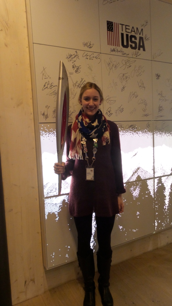 Me holding the torch at the USA House in front of the Olympian signature wall!